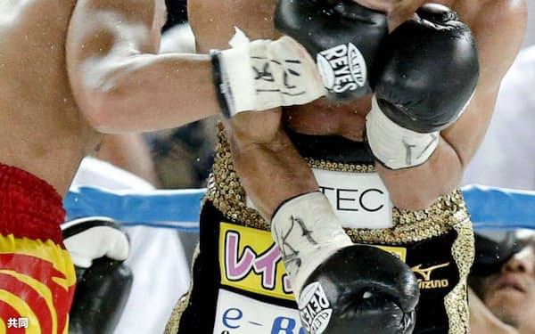 12回、テーパリット・ゴーキャットジム(左)の右を顔面に浴びる名城信男(1日、大阪市住吉スポーツセンター)=共同
