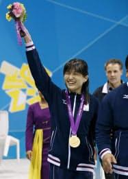 女子100メートル背泳ぎ(S11)で獲得した金メダルを胸に、声援に応える秋山里奈(2日、水泳センター)=共同