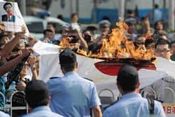 日本大使館前で日の丸を燃やす反日デモの参加者(15日、北京)=共同