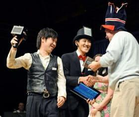「イグ・ノーベル賞」の「音響賞」を受賞する塚田浩二さん(左)と栗原一貴さん(20日、米マサチューセッツ州のハーバード大)=共同