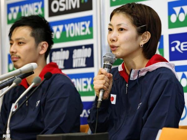 現役生活に幕を下ろし、記者会見するバドミントンの潮田玲子選手。左は池田信太郎選手(22日、東京・国立代々木競技場)=共同