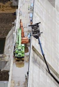 ダムの建設現場で横転し、宙づりになったクレーン車(24日、北海道新十津川町)=共同