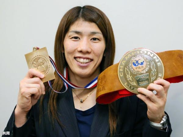 レスリングで前人未到の13大会連続世界一を達成し、金メダルと記念のベルトを手に笑顔を見せる吉田沙保里(1日午後、成田空港)=共同