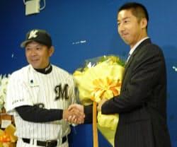 現役引退を表明し、ロッテの西村監督(左)と握手を交わす今岡打撃・守備コーチ兼内野手(5日、千葉市のQVC)=共同