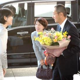 京都大学に到着し、職員(左)から花束を受け取る山中教授と妻の知佳さん(9日午前、京都市左京区)