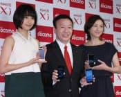 スマートフォンなどの新製品を発表し、記念写真に納まるNTTドコモの加藤社長(中)=10月11日午後、東京都中央区