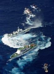 9月25日に沖縄県・尖閣諸島周辺の日本の領海に侵入し、放水する台湾の巡視船(上から4隻目)と漁船に放水する海上保安庁の巡視船(上から3隻目)=共同
