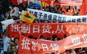 中国江蘇省蘇州で行われた反日デモで、「日本製品ボイコット」などと書かれた横断幕を掲げる参加者(9月)=共同