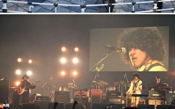日本武道館前に設置された太陽電池パネル(上)で作った電気で演奏する音楽祭「THE SOLAR BUDOKAN」(ソーラー武道館)。演奏する佐藤タイジさんの姿がスクリーンに映し出された(20日夜)=共同