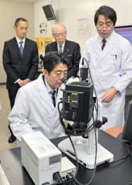 iPS細胞の研究施設を視察に訪れた安倍首相(手前)。奥左は山中伸弥京都大教授、同中央は野依良治理研理事長(11日、神戸市の理化学研究所)=代表撮影