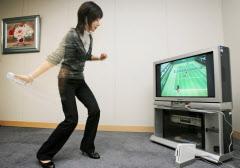 家庭用ゲーム機「Wii(ウィー)」。大型画面に向かってテニスの仮想ゲームを楽しめる