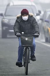 マスクをしながら自転車に乗る男性(29日、北京市内)=共同