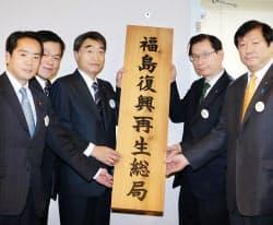 福島復興再生総局の看板を掲げる根本復興相(左から3人目)ら(2日、福島市)