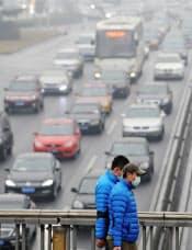 大気汚染が深刻化している北京市内でマスクを着けて歩く人たち(1月31日)=共同
