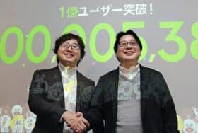 「LINE」の利用者数が1億人を突破し、握手するNHNジャパンの森川社長(左)と舛田執行役員(1月18日午後、東京都渋谷区)