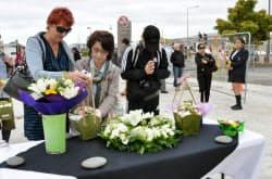NZ地震から2年。日本人が犠牲となったビルの倒壊跡地で献花する遺族ら(22日、クライストチャーチ)=共同