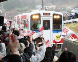 運行再開を祝う人たちに出迎えられ、吉浜駅に到着した三陸鉄道南リアス線の一番列車(3日、岩手県大船渡市)
