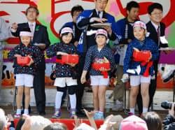 岩手県久慈市で海女の姿で観光をPRする「ちびっこあまちゃん隊」がお披露目された。祭りの来場者に餅をまいた(28日)=共同