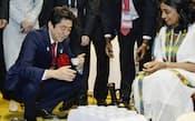 アフリカ開発会議に合わせ開催中の「アフリカン・フェア」で、エチオピアコーヒーを試飲する安倍首相(31日、横浜市西区)=共同