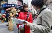 日本人観光客(右)と話すボランティア通訳(4月、ソウル)=ロイター