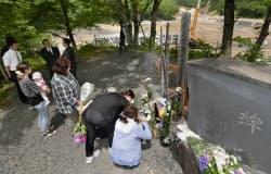 岩手・宮城内陸地震から5年、土石流で7人が犠牲になった「駒の湯温泉」跡地で慰霊碑に花を手向ける遺族ら(14日、宮城県栗原市)=共同