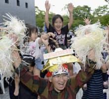 富士山の世界文化遺産登録が決まり、喜ぶ人たち(22日午後、静岡県富士宮市)=共同
