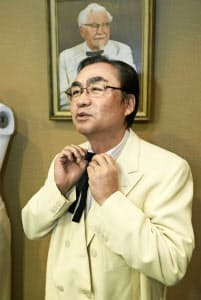 落札した故カーネル・サンダース氏のスーツを試着する日本ケンタッキー・フライド・チキンの渡辺正夫社長(22日、米テキサス州)=ヘリテージ・オークションズ提供・共同