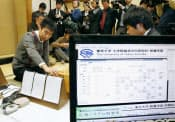 第2回電王戦の最終第5局で、将棋ソフト「GPS将棋」に敗れた三浦弘行八段(左、2013年4月20日、東京都渋谷区の将棋会館)=共同