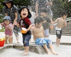 梅雨明けした東京都練馬区の公園で、噴水の水を浴び笑顔を見せる子どもたち(6日)=共同