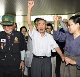 判決後に拳を掲げる原告の呂運沢さん(中央)と支援者ら(10日、ソウル高裁前)=共同