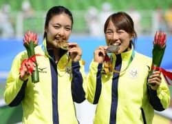 テニス女子シングルスの表彰式で笑顔を見せる優勝した石津幸恵(左)と3位の桑田寛子(カザニ)=共同