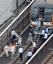 停電で止まった東急東横線の車両から降り、線路を歩く乗客ら(23日夜、川崎市中原区)=共同