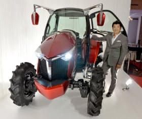 ヤンマーが発表したスポーティーなトラクターの試作機と工業デザイナーの奥山清行氏(25日、大阪市)=共同