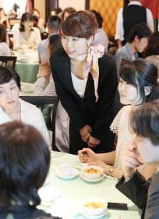 参加者に混ざって会話を楽しむ「ランチトリップ」主催者の松沢亜美さん(中央)=東京都港区の新北海園