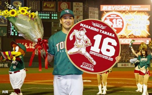 プロ野球新記録の開幕16連勝を達成し、花束とボードを手に笑顔を見せる楽天・田中投手(9日、Kスタ宮城)=共同