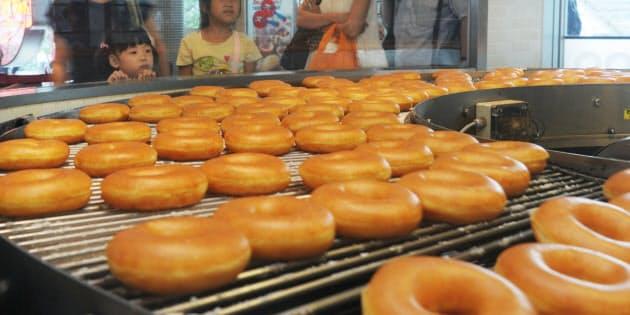 人気ドーナツ店「クリスピー・クリーム・ドーナツ」では店内の生産ラインから出てくるドーナツの行列が、列をなす人の目を楽しませる。並ぶ子供も「おいしそう」と待っている間じっと見つめていた(東京都渋谷区)