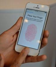アップルが発表した「iPhone5S」。指を乗せて指紋登録し、個人認証する(10日、米カリフォルニア州の本社)