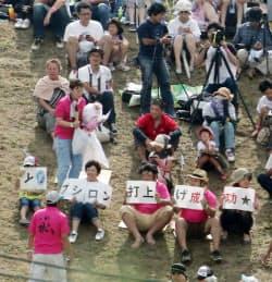 「イプシロン打ち上げ成功」と書かれた紙を掲げる人たち(14日午後、鹿児島県肝付町)
