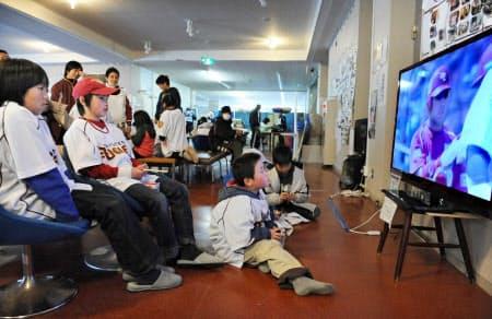 避難所に設置されたテレビで楽天の試合をユニホーム姿で観戦する子どもたち(11年4月12日、宮城県女川町)