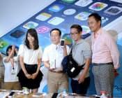発売された「iPhone5s」を受け取り笑顔を見せる男性=右から2人目(20日午前、東京都千代田区のドコモショップ丸の内店)