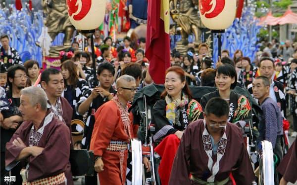 岩手県久慈市の秋祭りのパレードに能年玲奈さん(右)と宮本信子さんが人力車に乗って参加(20日)=共同