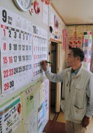 仮設住宅の集会所でカレンダーに催しの予定を書き込む佐藤政信さん(9月30日、仙台市宮城野区)