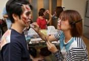 仕事旅行社が企画した特殊メイクの職業体験ツアー。参加者が互いの顔にゾンビのメイクを施す(東京都江戸川区の自由廊アトリエ)