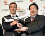 模型を手に記念写真に納まる日本航空の植木義晴社長(右)とエアバス社のファブリス・ブレジエ社長兼CEO(7日午後、東京都港区)=共同