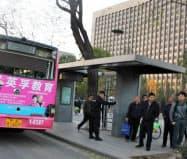 現場には窓が吹き飛んだバスがそのまま止まっていた。後方は共産党委員会のビル(6日、山西省太原市)