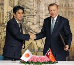 トルコのエルドアン首相(右)と握手を交わす安倍首相(10月29日、トルコ・イスタンブール)=共同