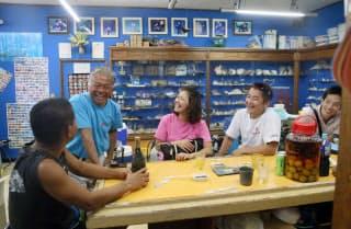 海底貯蔵の泡盛で作った梅酒などを飲みながら、ダイビングで出合った生き物を振り返る。沖縄の海を知り尽くした玉栄さん(左から2人目)の話に花が咲く(沖縄県うるま市のダイビングショップ「マリンスペース」)