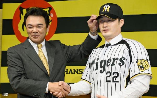 阪神の入団記者会見を終え、和田監督(左)と握手する呉昇桓投手(13日午後、大阪市内のホテル)=共同