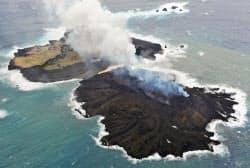 活発な火山噴火で西之島(奥)とつながった「新島」(26日午後、東京都小笠原村)=共同