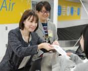 地上勤務社員の研修でチケットを発券するスタッブ記者(左)=成田空港